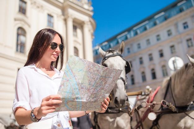 Touristisches mädchen der reise mit karte in wien draußen während der feiertage in europa, Premium Fotos