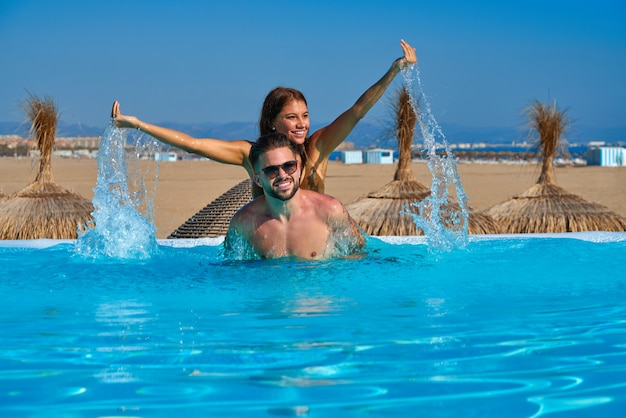 Touristisches paar huckepack im infinity-pool Premium Fotos