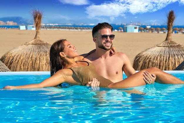 Touristisches paarbad im infinity-pool am strand Premium Fotos