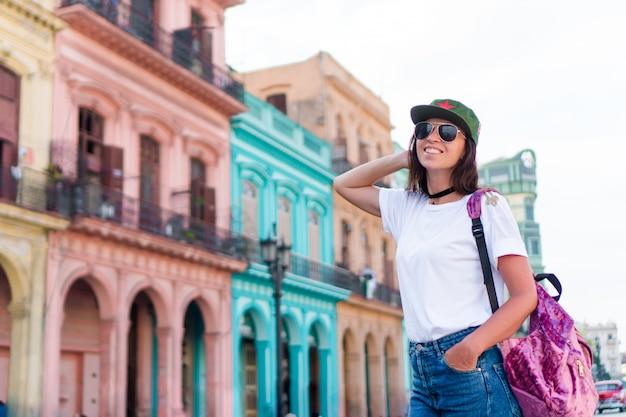 Touristisches schönes mädchen im populären bereich in altem havana, kuba. reisendlächeln der jungen frau glücklich. Premium Fotos