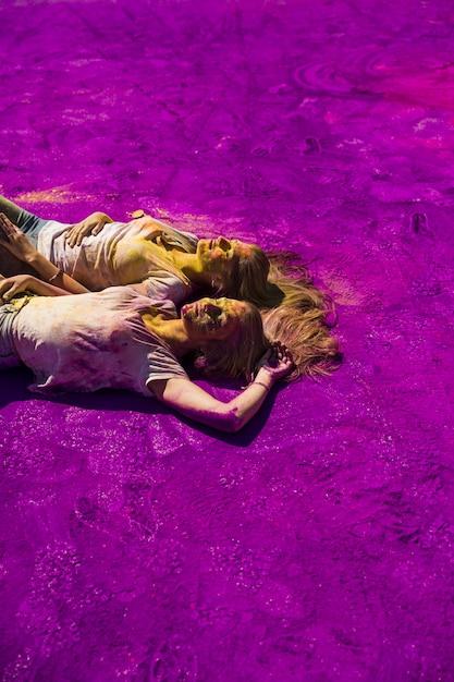 Tow junge frau, die auf purpurroter holi farbe sich entspannt Kostenlose Fotos