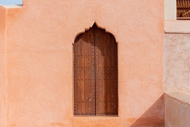 Traditionelle arabische architektur, holztür im muslimischen stil und rote lehmwand Premium Fotos