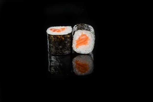 Traditionelle frische japanische sushirollen auf einem schwarzen hintergrund Premium Fotos