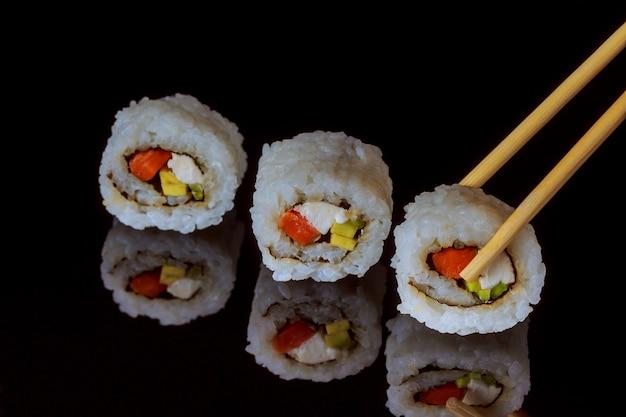 Traditionelle frische japanische sushirollen auf schwarzem hintergrund Premium Fotos