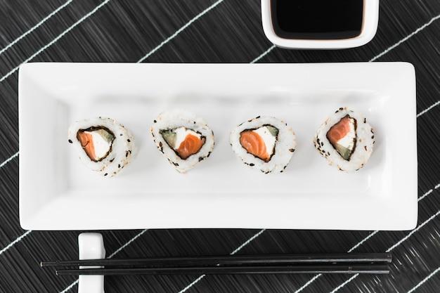 Traditionelle geschmackvolle sushi im weißen behälter mit soße und essstäbchen Kostenlose Fotos
