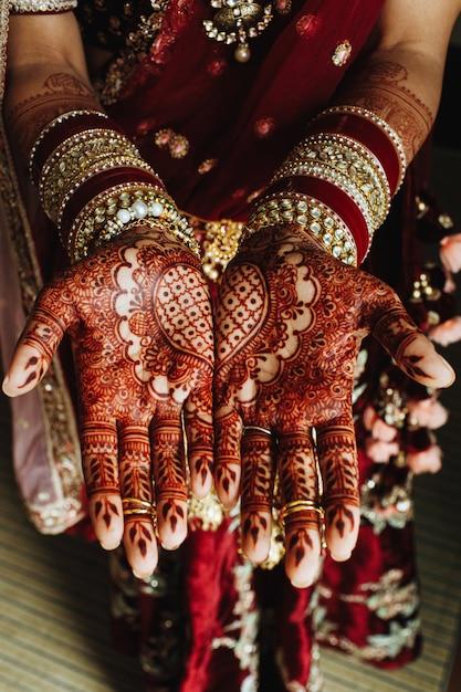Traditionelle indische herzverzierung auf den händen gefärbt durch hennastrauch und brautarmbänder in den bordeauxfarben Kostenlose Fotos