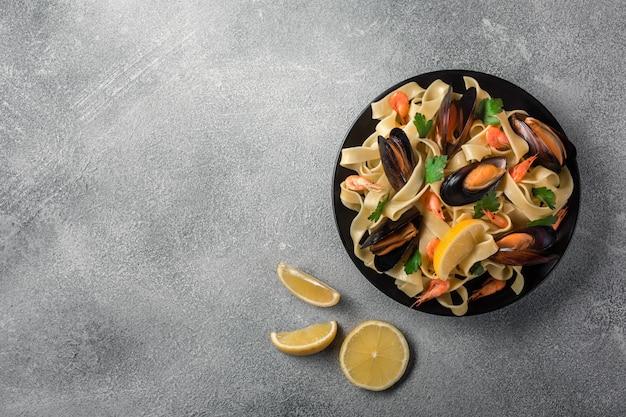 Traditionelle italienische meeresfrüchteteigwaren mit muschelspaghettis alle vongole auf steinhintergrund Premium Fotos
