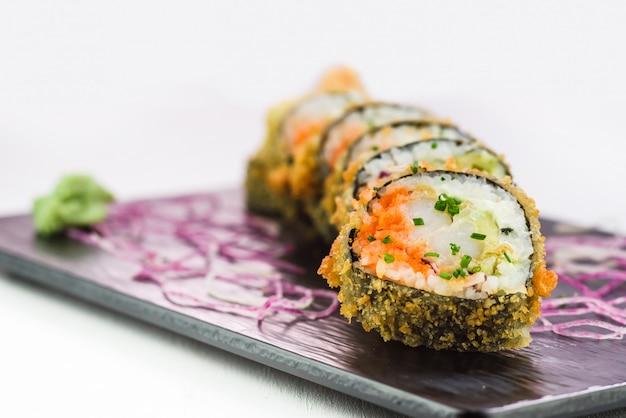Traditionelle japanische rollen und sushi auf einer schwarzen steinplatte Premium Fotos