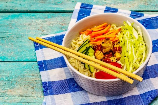 Traditionelle koreanische nudelschale mit geräuchertem hähnchen, frisch geschnittenem gemüse und sesam Premium Fotos