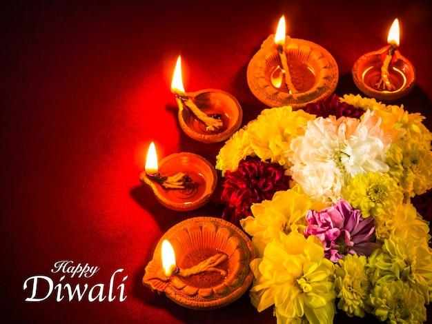 Traditionelle lehm-diya lampen beleuchteten mit blumen für diwali-festivalfeier. Premium Fotos