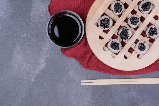 Traditionelle maki-sushi-rolle mit stäbchen und sojasauce auf roter tischdecke. Kostenlose Fotos