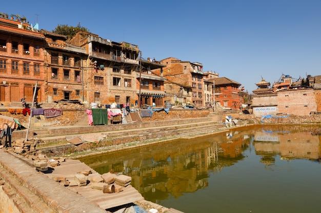 Traditionelle nepalesische newar-häuser nahe dem grünen teich in bhaktapur, nepal Premium Fotos