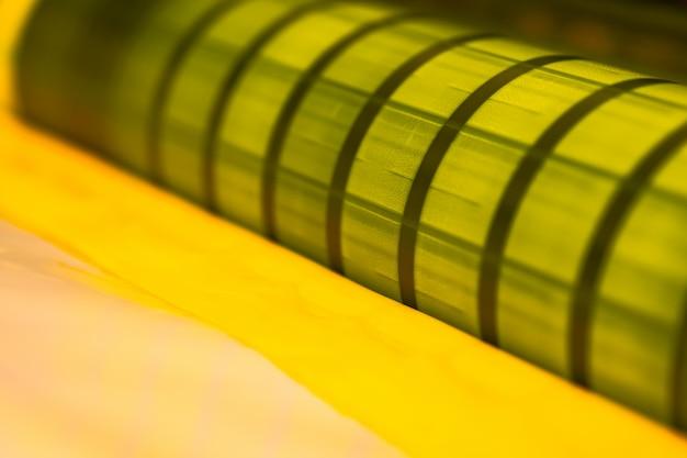 Traditionelle offsetdruckmaschine. drucken in tinte mit cmyk, cyan, magenta, gelb und schwarz. grafik, offsetdruck. detail der druckwalze in der offsetmaschine von vier körpern gelber tinte Premium Fotos