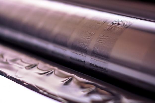 Traditionelle offsetdruckmaschine. drucken in tinte mit cmyk, cyan, magenta, gelb und schwarz. grafik, offsetdruck. detail der druckwalze in der offsetmaschine von vier körpern schwarzer tinte Premium Fotos