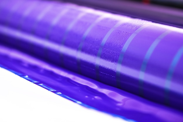 Traditionelle offsetdruckmaschine. drucken in tinte mit cmyk, cyan, magenta, gelb und schwarz. grafik, offsetdruck. druckmaschine auf offsetmaschine mit vier körpern cyan-tinte Premium Fotos