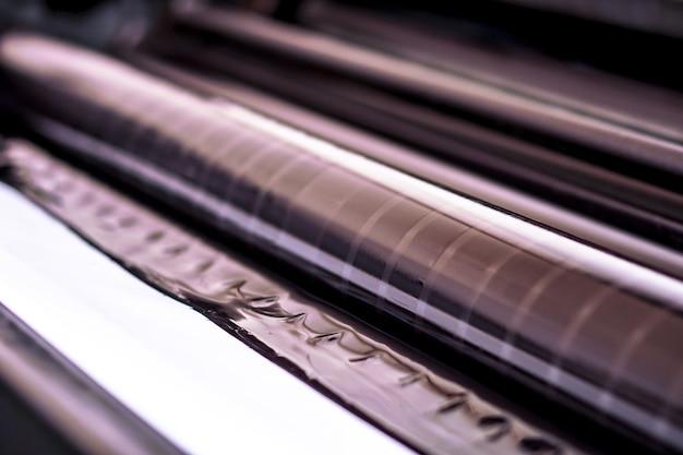 Traditionelle offsetdruckmaschine. drucken in tinte mit cmyk, cyan, magenta, gelb und schwarz. grafik, offsetdruck. offsetdruckwalze mit vier schwarzen tintenkörpern Premium Fotos