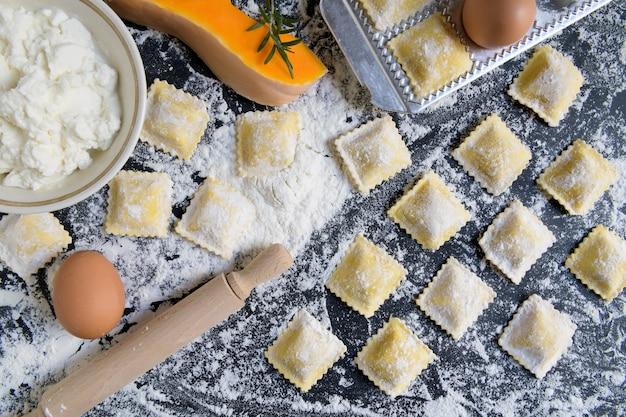 Traditionelle rohe ravioli mit kürbis auf einem holztisch mit mehl, handgemacht, garprozess Premium Fotos