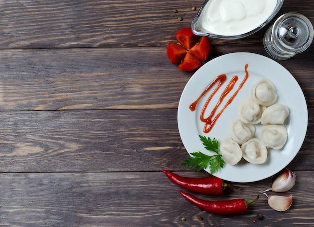 Traditionelle russische mehlklöße, ravioli, pelmeni auf einer weißen platte mit roter soße und petersilie. Premium Fotos
