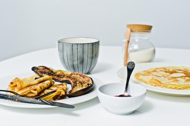 Traditionelle russische pfannkuchen mit blaubeermarmelade, frühstück mit kaffee. Premium Fotos