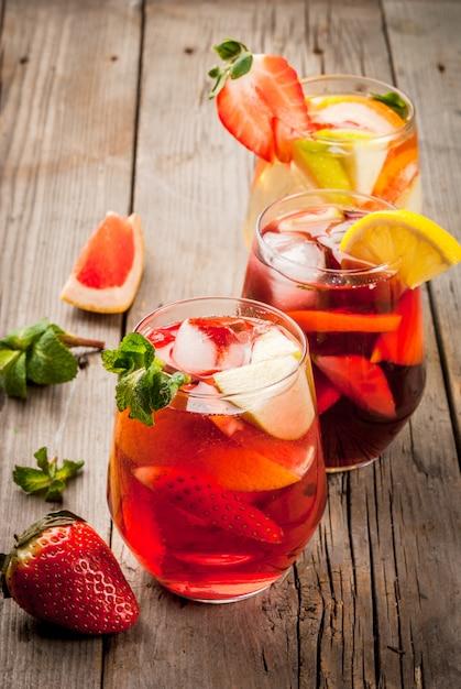 Traditionelle sommergetränksangria - rot, rosa und weiß. mit champagner, rosé und rotwein und früchten Premium Fotos