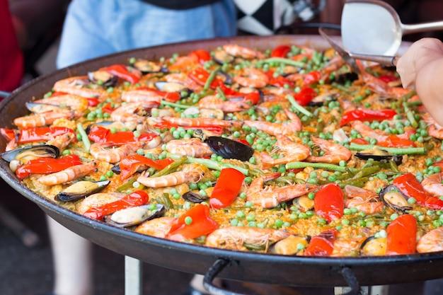 Traditionelle spanische reispaella mit meeresfrüchten. gemischter meeresfrüchteaufruhr gebraten würzig und salat. würzige meeresfrüchte. Premium Fotos