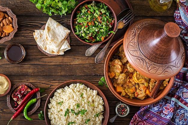 Traditionelle tajine-gerichte, couscous und frischer salat auf rustikalem holztisch. tajine lammfleisch und kürbis. ansicht von oben. flach liegen Premium Fotos