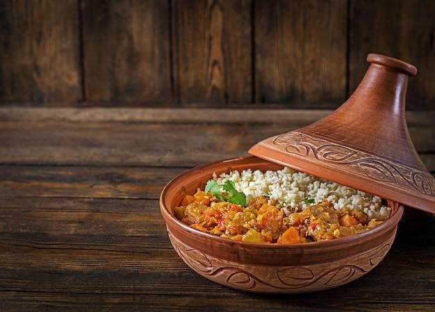 Traditionelle tajine-gerichte, couscous und frischer salat auf rustikalem holztisch. tajine lammfleisch und kürbis. Premium Fotos