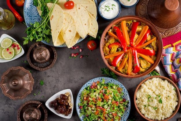 Traditionelle tajine-gerichte, couscous und frischer salat auf rustikalem holztisch. Premium Fotos