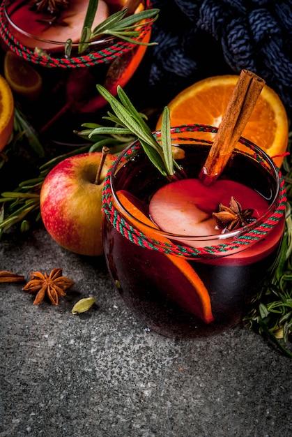 Traditionelle winter- und herbstgetränke. weihnachts- und thanksgiving-cocktails. glühwein mit orange, apfel, rosmarin, zimt und gewürzen auf dunklem stein, Premium Fotos