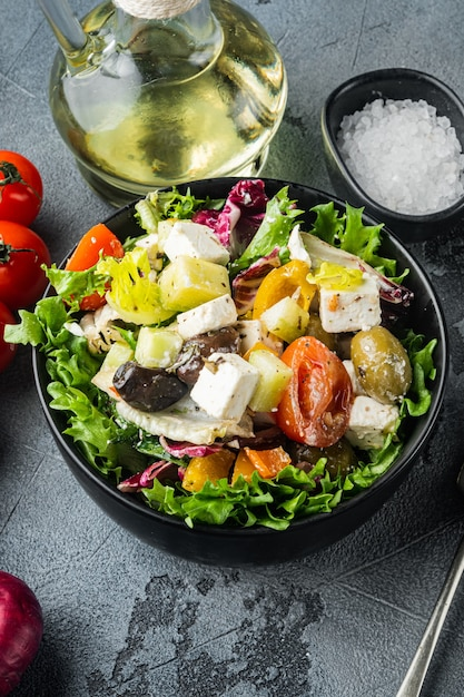 Traditioneller griechischer salat mit frischem gemüse, feta und oliven, auf grauem tisch, draufsicht flach gelegt Premium Fotos