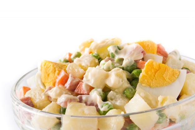 Traditioneller russischer salat, olivier-salat lokalisiert auf weiß. ansicht von oben. Premium Fotos