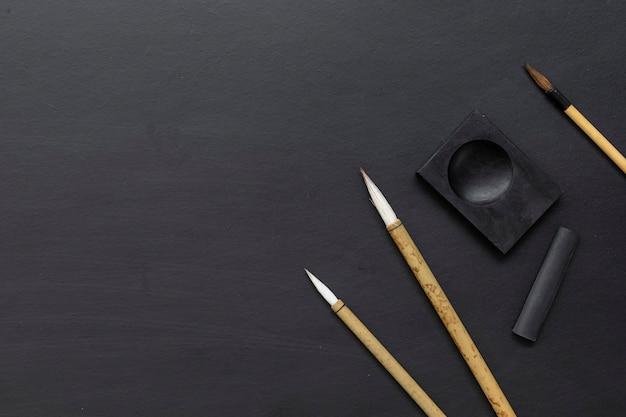 Traditioneller schreibpinsel der nahaufnahme japan auf schwarzem tisch. draufsicht. flach liegen Premium Fotos