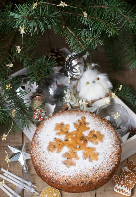 Traditioneller weihnachtsfruchtkuchen auf einem kasten mit weihnachtsspielwaren und -tannenzweigen. Premium Fotos