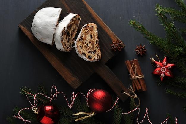 Traditioneller weihnachtskuchen mit rosinen und nüssen mit baumasten und spielwaren Premium Fotos