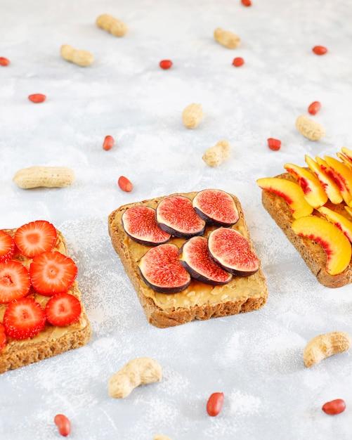 Traditionelles amerikanisches und europäisches sommerfrühstück: sandwiche des toasts mit erdnussbutter, draufsicht der kopie Kostenlose Fotos