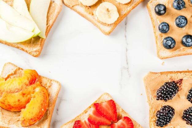 Traditionelles amerikanisches und europäisches sommerfrühstück: toastsandwiches mit erdnussbutter, beere, fruchtapfel, pfirsich, blaubeere, blaubeere, erdbeere, banane. weißer marmortisch. copyspace draufsicht Premium Fotos