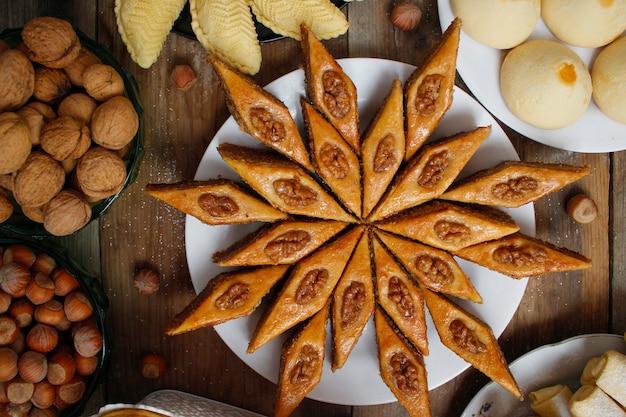 Traditionelles aserbaidschan-feiertagsplätzchenbaklava auf weißer platte auf dem rustikalen hintergrund Premium Fotos