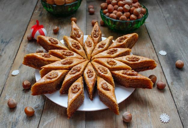 Traditionelles aserbaidschan-feiertagsplätzchenbaklava auf weißer platte auf dem rustikalen mit nüssen Premium Fotos