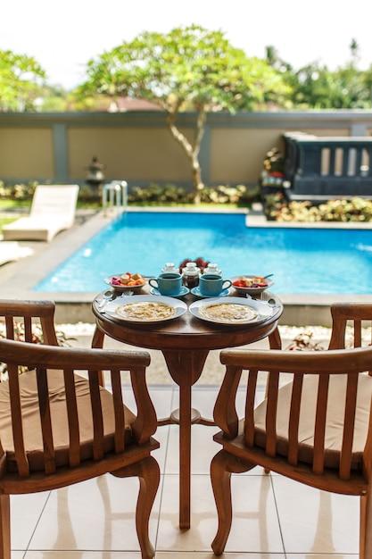 Traditionelles balinesse frühstück mit zwei blauen schalen heißem getränk auf holztisch Premium Fotos