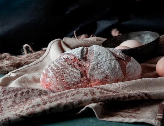 Traditionelles brot mit weißmehl auf ihm mit eierschüssel herum auf einem rustikalen tuch. Kostenlose Fotos