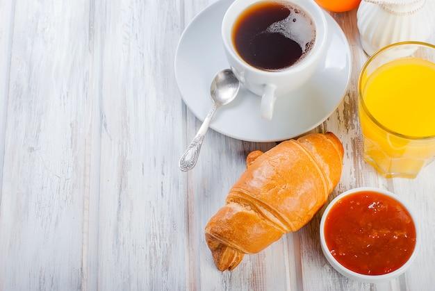 Traditionelles frühstückshörnchen und kaffee, marmelade, orangensaft Premium Fotos