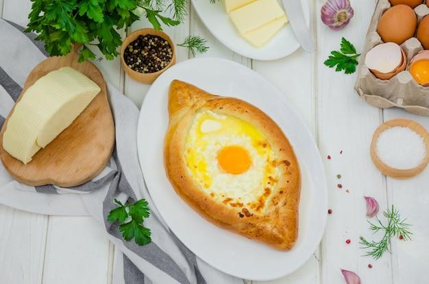 Traditionelles georgisches käsegebäck ajarian khachapuri mit eiern und butter auf einer platte auf einer weißen holzoberfläche Premium Fotos