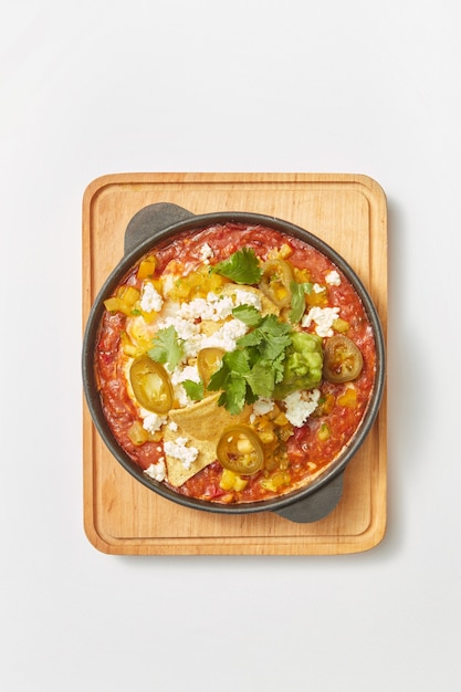 Traditionelles gericht des nahen ostens shakshuka aus spiegeleiern mit tomaten, paprika, gemüse und kräutern in einer pfanne auf einem holzbrett auf hellgrauem hintergrund, kopienraum. draufsicht. Premium Fotos