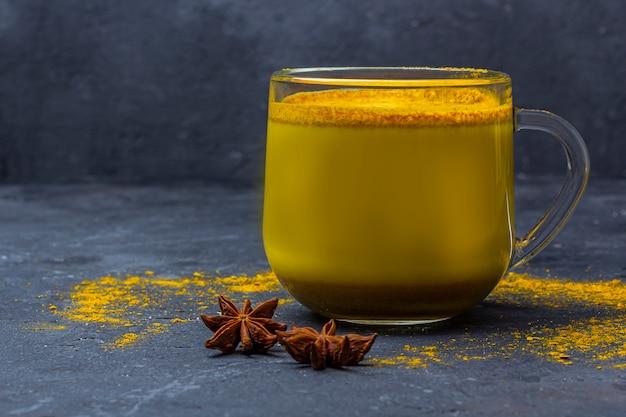 Traditionelles indisches getränk kurkuma milch ist goldene milch in glasbecher mit zimt, anis stern, kurkuma auf dunklem hintergrund. gewichtsverlust, gesundes und biologisches getränk Premium Fotos