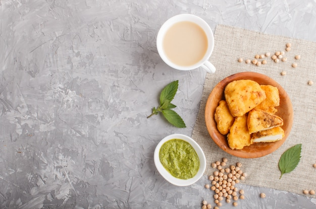 Traditionelles indisches lebensmittel paneer pakora in der hölzernen platte mit tadellosem chutney auf einem grauen konkreten copyspace. ansicht von oben. Premium Fotos