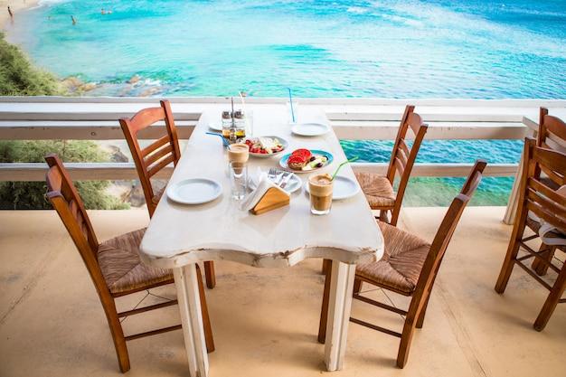 Traditionelles mittagessen mit köstlich frischem griechischem salat, frappe und brusketa zum mittagessen im restaurant im freien mit herrlichem blick auf das meer und den hafen Premium Fotos