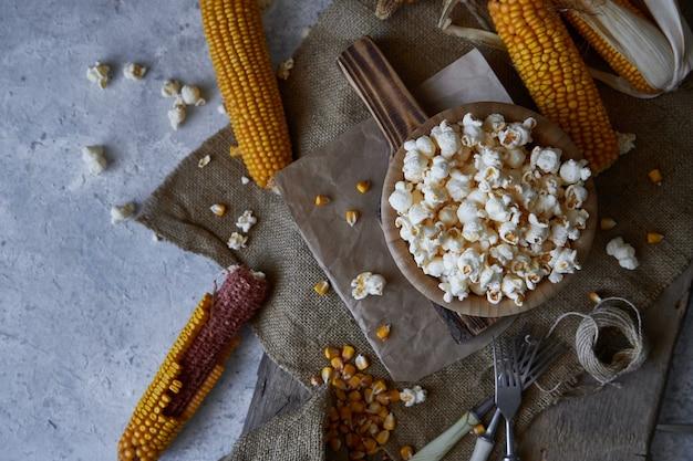 Traditionelles popcorn in einer hölzernen schüssel und in maiskolben auf dem tisch. Premium Fotos