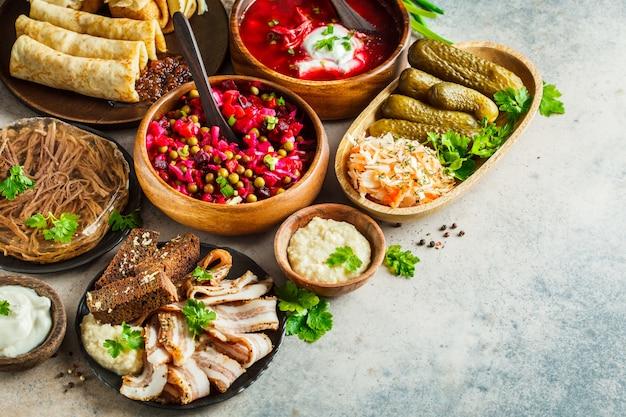 Traditionelles russisches küchekonzept. borschtsch, geliertes fleisch, schmalz, crepes, salatvinaigrette und sauerkraut, grauer hintergrund. Premium Fotos