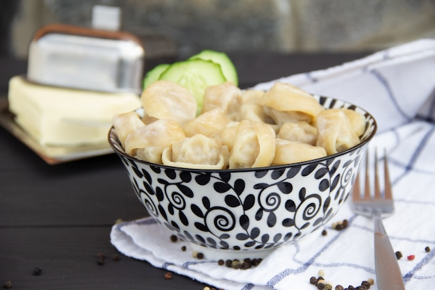 Traditionelles russisches pelmeni in der platte auf rustikalem holztisch. hausgemachte knödel. halbfertige produkte. Premium Fotos