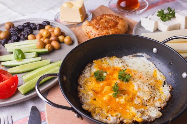 Traditionelles türkisches frühstück - spiegeleier, frisches gemüse, oliven, käse, kuchen und tee Premium Fotos